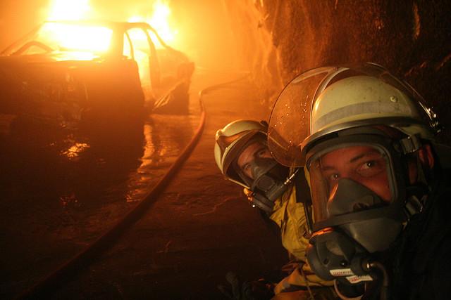 Zwei Feuerwehrleute vor einem brennendenFahrzeug
