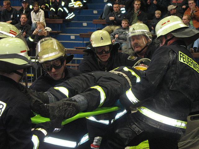 Feuerwehrleute tragen Person auf Spineboard