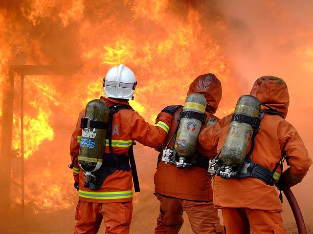 Drei Feuerwehrleute vor einer Flammenwand
