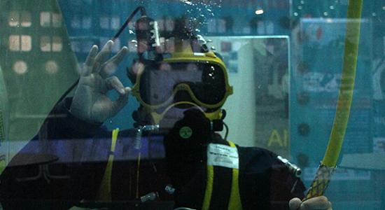 """Ein Feuerwehrtaucher zeigt unter Wasser """"Alles OK"""""""