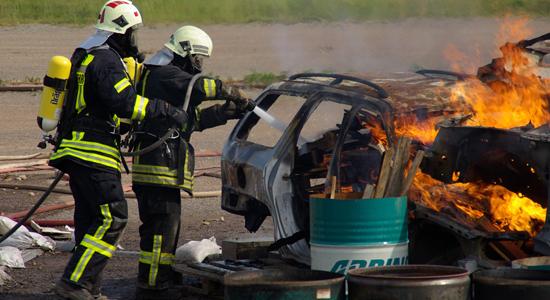Ein Feuerwehrtrupp erkundet ein brennendes Auto