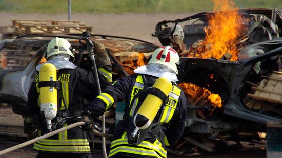 Zwei Feuerwehrleute bekämpfen einen Autobrand